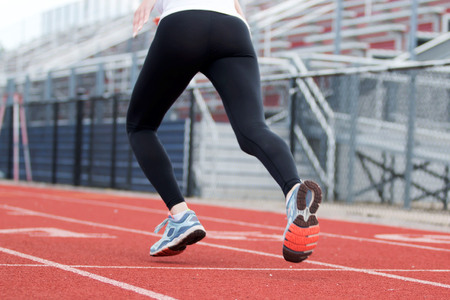 spandex: A female high school track runner starts her sprint down the track