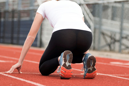 spandex: Female High school track sprinter in the on your mark, position ready to race down the track in the one hyndred meter dash Stock Photo