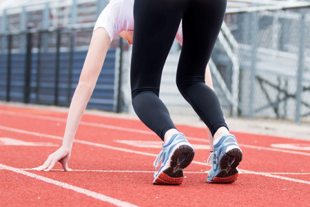 spandex: A felmale high school sprinter is in the set position on a red track