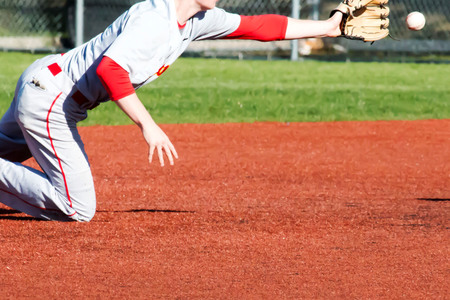 A shortstop dives fot the ball during a baseball game on a red turf infield Imagens - 80481683