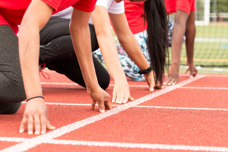 Three high school girls are ready to start a sprint race during track and field practice