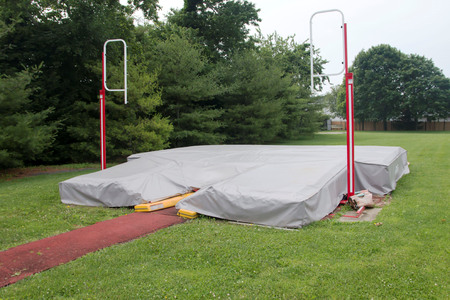 A local high school pole vault pit is coverd up with a gray tarp Stock fotó - 82414522