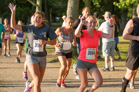 Babylon, NY, USA - 26 June 2017: Two female runners waving at camera during the Belmont Lake State Park summer series 5K race. Sajtókép