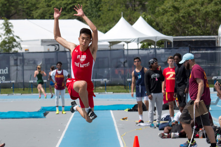 A male high school athlete triple jumps during the CHSAA Catholic State Championships in New York on Saturday May 21, 2017 at Icahn Stadium.