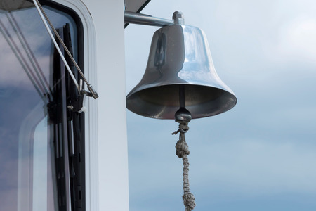A large silver bell hangs on the outside of a ferry boat