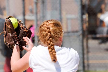 Een middelbare schoolmeisje met rood haar, vangt net een geel softbal aan haar linkerkant Stockfoto