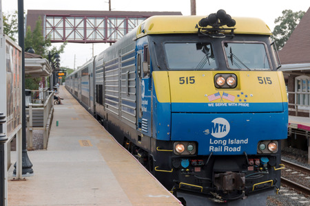 Bay Shore, NY, USA - 29 June 2017: A double decker train arrives at the Bay Shore train station the week before the Summer of hell is to begin.