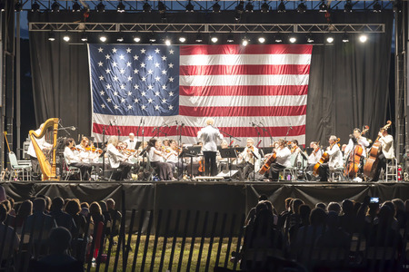 cellos: East Islip, NY, USA - 15 July 2017: The new Long Island Concert Orchestra performs for free at night, under the stars, at Heckshire State Park to honor our hometown heroes.