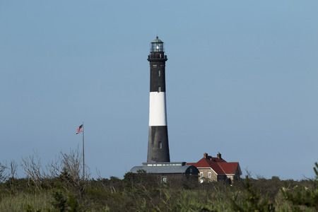 The Fire Island Lighthouse picture taken from the west with a deep blue sky and the light shining out of the top
