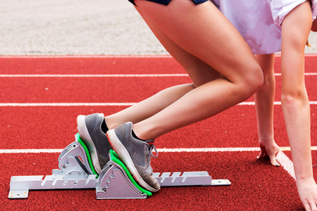 bounding: A high school female practice coming out of the blocks in track and field practice on a red track.