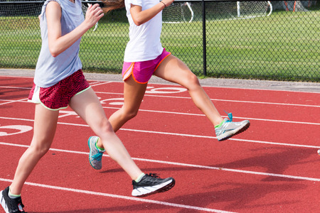 Two high school track and field athletes perform straight leg bounding on a red track at practice outside Stock Photo