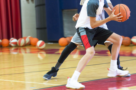 Two teenage male basketball players doing a one on one drill indoors at a local basketball camp over the summer. Stockfoto