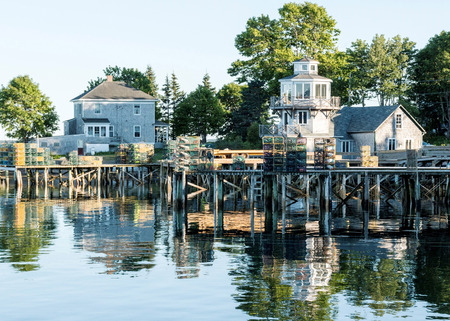 The coastline of bass harbor Maine with houses, trees, and their lobster traps stacked on docks all reflecting in the water