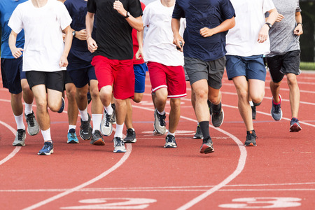 High school boys running in a large group on a red track during cross country practice. Stockfoto