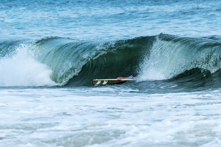 coordinacion: Surfer hangs on to his board as he is about to be engulfed in a wave in thte early evening at Robert Moses State Parks, Fire Island, New York