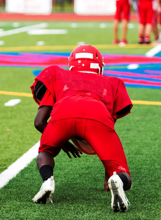 A high school football player at practice in a three point stance on a green turf field in all red clothing,