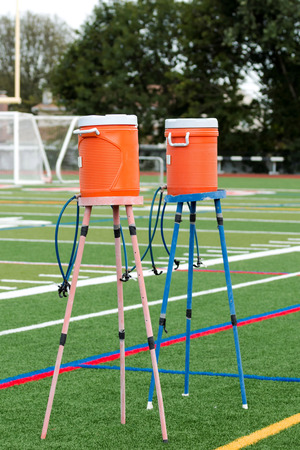 Two water coolers on stands with multiple spouts to hydrate athletes practicing on a green turf field. Stock Photo