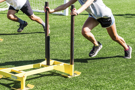 Two cross country runners pushing weighted sleds on a green turf field on a sunny day