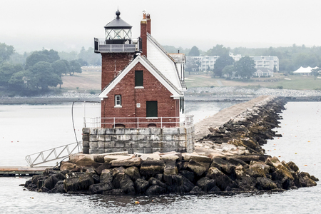 The Rockland Breakwater Lighthouse taken from the water with the getty walkway and land in the background,
