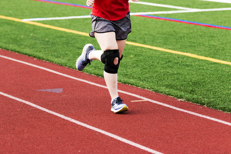 A runner is practicing on a red track while wearing a large black knee brace.