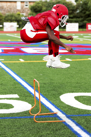 A high school football player is jumping over orange mini hurdles during agility practice on a local turf field.