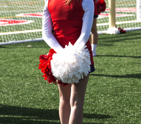A high school cheerleader is standing tall with her red and white pompoms behind her.