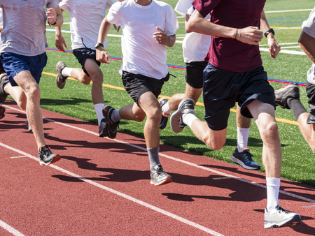 A boys cross country team running quick while in a group, on a track at practice.