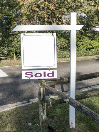 A real estate sign is placed on a corner to advertise a house was for sale and is now sold with a fence under and trees in the background. Stock Photo