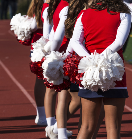 A few cheerleaders watch the football game rooting for their home team.
