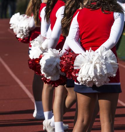Een paar cheerleaders kijken naar het voetbalspel dat wortelt voor hun thuisteam.