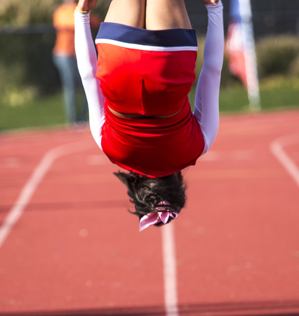 A high school cheerleader doing a flip during a time out of the football game. Stock Photo