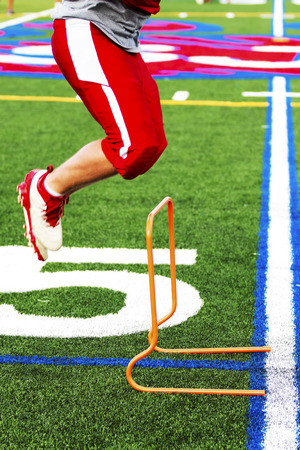 A high school football player is cross training by jumping over orange mini hurdles at practice on a green turf field. Stock Photo