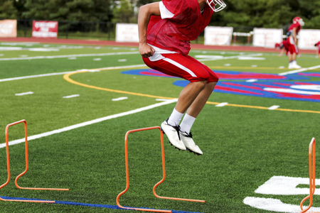A high school football player is jumping orange hurdles at a preseason football practice on a green turf field. Stock Photo