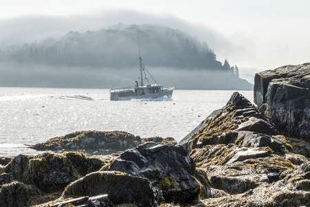A lobster boat is heading out of Bar Harbor Maine with porcupine island covered by the fog in the background.