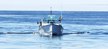 Un pescador está sacando una trampa de langosta del Océano Atlántico usando un poste para agarrar la cuerda debajo de una boya anaranjada frente a la costa de Maine. Foto de archivo