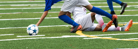 A high school soccer player using a slide tackle on his opponent during a game on a green rutf field.