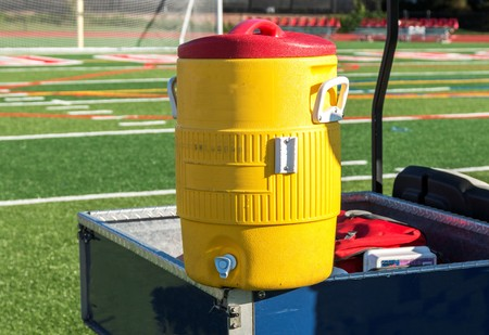A yellow water cooler sits on a blue golf cart during a soccer game at a local high school on a bright sunny afternoon.