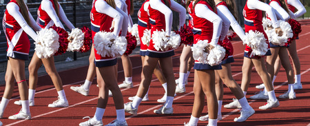 High school cheerleaders cheering on the crowd at a football game on a sunny afternoon in the fall.