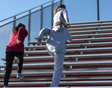 High school girls warm up on a fall day by running bleachers before practice on a sunny fall afternoon. Stok Fotoğraf - 91268331