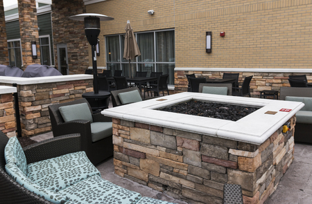 A relaxing area is set up outside of an upstate new york hotel that has a fire pit, couches, chairs and a heat lamp.