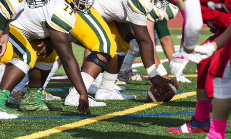 Two football teams are lined up for the snap of the football on a green turf field. One team is wearing gold and white colors and the other is red and white.