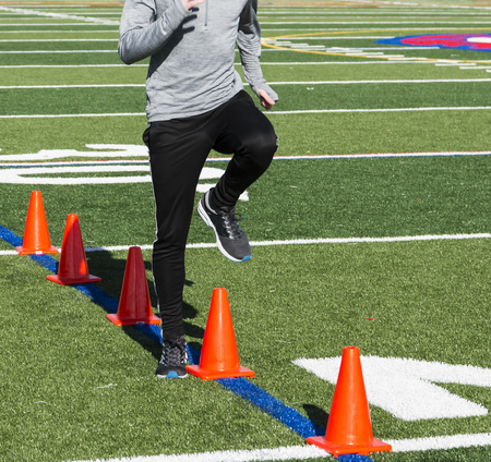 A runner performes speed drills over orange cones on a green turf field during high school athletics practice on a sunny autumn afternoon.