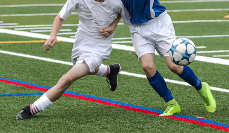 Two male soccer players are fighting for the ball during a soccer game. One is in a white uniform and tho other is in a blue top and white shorts.