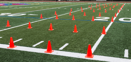 A green turf field is set up with orange cones for athletes to perform agility and speed training during practice. Banco de Imagens