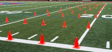 Een groen grasveld is opgezet met oranje kegels voor atleten om behendigheids- en snelheidstraining tijdens de training uit te voeren. Stockfoto