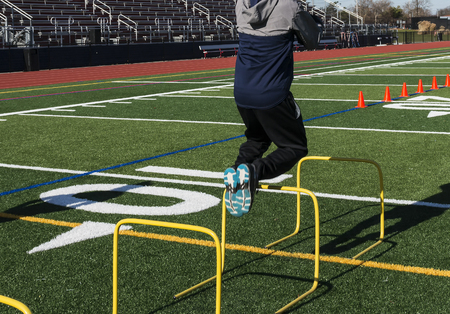 A track and field athlete jumping over yellow mini hurdles on a turf field from behind the runner.