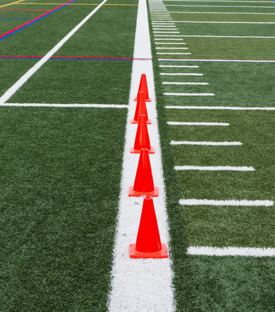 Orange cones are placed on a thick white line so runners can perform speed drills over them on a green turf field. Stock Photo