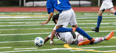 Two male soccer players fight for the ball and one slide tackles in an attempt to gain an advantage, Stock Photo