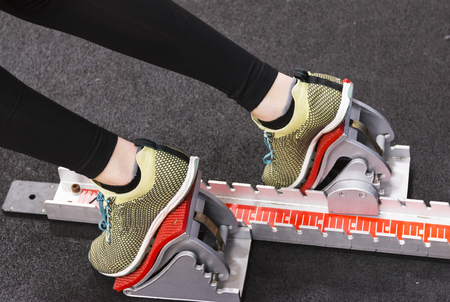A sprinters legs and feet in the starting blocks at indoor practice on a portable track. Stock Photo