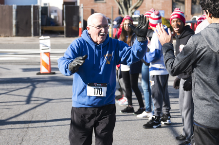 West Islip, NY, USA - 24 November 2017: A runner receives high fives from the school track team as he approaches the end of the annual Run Your Turkey Off 4K turkey trot.